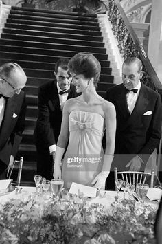 Three men wait while Jackie Kennedy is seated at a dinner for the America's Cup Race, at the Breaker's Estate.  First Lady Jacqueline Kennedy Pictures | Getty Images