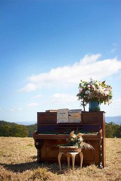 Piano outside in a field & vase of flowers on top