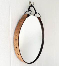 Bedeck your bedroom with some equestrian fancy. This wood-mounted beveled mirror is wrapped and embellished with a weathered Latigo leather girth and vintage twisted snaffle bridle bit, evoking the stylings of British campaign furniture. It hangs on the wall from the bit, the framed mirror fit for a dressing room, entryway or stable space.
