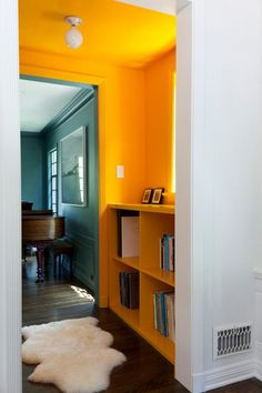 Lovely Interiors: Orange + White Walls • Create a fake wall near windows to place a shelf or Ottoman chair