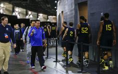 Kansas head coach Bill Self lifts his water bottle in acknowledgement of the Michigan Wolverines players as they head to their locker room after a practice at Cowboys Stadium in Arlington, Texas on Thursday, March 28, 2013.