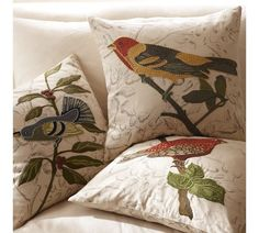 Bright colored embroidered birds on subtle design pillow