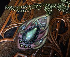 Fantasy labradorite pendant - Hand tooled leather pendant with teardrop labradorite and bronze chain - Artisan jewelry by Gemsplusleather on Etsy - 33.33$ #tooledleather #leathercraft #leather #labradorite #pendant #handmade  #iridescent #fantasy #LARP #jewelry #jewellery #Gemsplusleather #art #artisan #cosplay #boho #bronze #chain #rainbow #gypsy #mahogany #burgundy