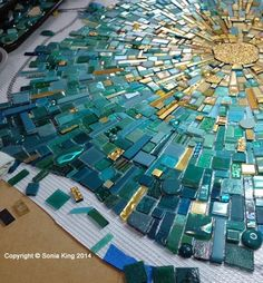 The light aqua color surrounding the burst of golden energy is darkening to teal at the edge of the first of eight elements. Sonia King project.