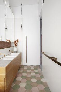 In bagno, rubinetti in ottone grezzo Vola. Le lampade sono le Well Glass Pendant Light di Dunlin. Arredi su disegno in legno e corian. Piastrelle di Popham Design
