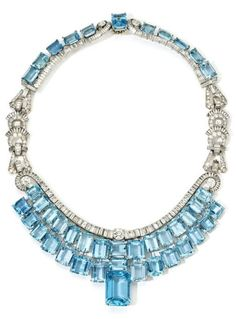 An Art Deco aquamarine and diamond necklace, by Olga Tritt, New York, 1939. Suspending graduating rectangular aquamarines, surmounted by a scroll of calibre cut diamonds emanating and centred by round brilliant cut diamonds, the back of the necklace curved to fit the neck and similarly set with aquamarines below an articulated diamond scroll, the front and back joined by geometric and fan shaped links mounted with brilliant and calibre cut diamonds. #OlgaTritt #ArtDeco #necklace