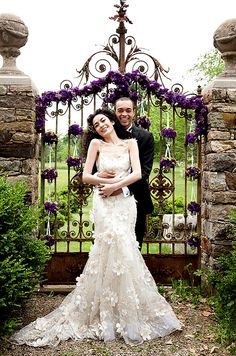 Romance personified: showing the love in formal attire before a gate adorned in dark purple flowers.