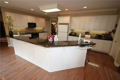Interesting charging station on end of island.  White cabinets with traditional, white freezer-over-fridge.   2805 Woodsgate Drive, Little Rock AR - Trulia