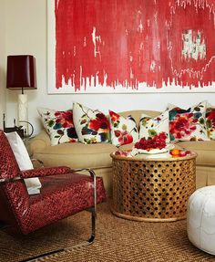 A large, eye-catching painting by Veronica Volani-Inza adds spice to the sitting area. Fun floral pillows by Rubelli cover the Duralee-upholstered sofa, encouraging guests to snuggle up with a good read.