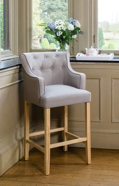 Compliment your kitchen with this grey upholstered cushioned button barstool. With natural rubber wood oak legs, this sleek stool offers a complimenting foot rest and is a great way of adding luxury to your home. With its high buttoned back and sophisticated curved arms, this chair fuses traditional elements with a modern twist. Also available in natural