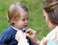 In a tender moment, the Duchess of Cambridge helps undo the buttons on her daughter's blue knit cardigan
