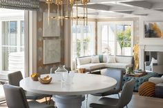 Contemporary dining room boasts a brass chandelier illuminating a round white lacquered dining table lined with gray leather dining chairs facing a sunken living room.