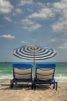blue lounge chairs with blue and white striped umbrella