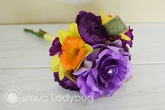 Purples and daffodils surround this Alice in Wonderland themed bridesmaids bouquet.
