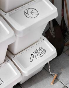Close-up van gestapelde witte opbergdozen met een tekening die toont wat erin zit