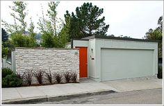 Mid Century home with red door and stone wall