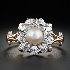 An original Victorian beauty highlighting a shimmering natural button pearl with cream-rose overtones situated in the center of a sparkling wreath of old mine-cut diamonds. The diamonds are set in platinum and glisten atop a yellow gold ring shank with a gracefully scrolled shoulder design. As lovely as can be.