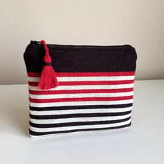 **Handmade** Black, Red and White Stripe Woven Fabric Zippered Pouch / Cosmetic Bag / Make up bag / Coin Purse This zipper pouch is made using black woven fabric and fully lined with black cotton fabric and closes with black color zipper. I also add red and black color coton tassel for