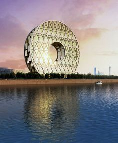 The 'Guangzhou Circle Mansion' in Guangzhou, China. By Italian Architect Joseph Di Pasquale of Milan. The landmark is defined by its strong reference to the iconic double jade disk, a royal symbol of the ancient chinese dynasty that reigned in the area around 2000 years ago. Reflecting onto the water below, the structure completes a mirror image, enhancing this symbolic image. stepping away from a typical vertical skyscraper form, the circular building reaches a total height of 138m