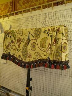 Gently shaped valance with fringe, side knife pleats, and covered buttons. Judy Peters, www.palmettodrapery.com