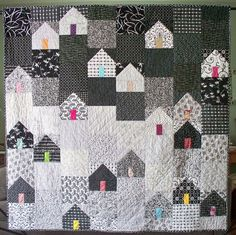"""""""Bee's Knees"""" by Debbie Grifka at Esch House Quilts, who says: """"The black and white houses and background and all the different doors to the houses contributed by my fellow Bee's Knees group give me the feeling of a cheerful, snug community on a snowy night."""""""