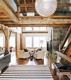 Foyer in a repurposed barn home with capiz shell globe pendant light, striped rug, tufted leather bench, two white arm chairs facing a window