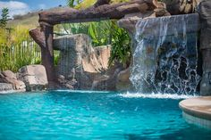 Materials: Tropical beach entry custom swimming pool with a perimeter flow spa, grotto, rock slide, and waterfalls. Custom outdoor kitchen with swim up bar seating. Plaster – StoneScapes Caribbean mini pebble plaster Decks – Flagstone and sand finish colored concrete Coping – Precast Tile – Travertine