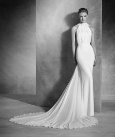 NOEMI is a halter neck wedding dress in crepe and gauze embellished with gemstones with a mermaid silhouette that highlights the delicacy of the design.