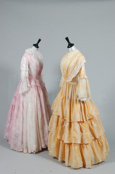 Two printed cotton 1850s day dresses, the first of pink and white trellis-weave muslin printed with fruits, fan-pleated front bodice with peplum to the waist; the other of mustard and white roller printed cotton with pagoda sleeves, tiered skirt