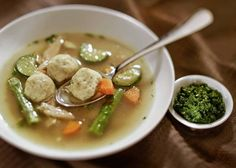 A Sephardi chicken soup with herb-flecked kneidelach is served with zehug, a chile-garlic relish, on the side.