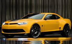 2014 Chevrolet Camaro Bumblebee Concept - from 2014 Transformers 4 movie ..Using a base from the standard Camaro, Bumblebee takes on a face of its own with sleeker headlights, a larger grille, and in the back, a wider set of rear fenders.  Some custom high-spoke wheels fit nicely onto a set of Goodyear tires, all pulled together with a signature yellow paint scheme with black racing stripes, naturally.  found on - http://www.boldride.com/ride/2014/chevrolet-camaro-bumblebee-concept#gallery/2