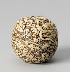 A highly unusual ivory spherical manjû of a dragon. 19th century. In two parts, carved all over with a running dragon amidst waves, holding a jewel, with clouds on the top. Inscribed Tadatoshi in a sunken reserve.