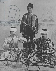 SIC 743467    An image of Monahan Levi, Isaac Cohn and H Hondon, Turkish Jews seen here smoking the Nahrgeela (water pipe) and drinking Turkish coffee at the World's Columbian Exposition in Chicago, Illinois, 1893. This image was published in the book 'Oriental and Occidental Northern and Southern Portrait Types of the Midway Plaisance' by N.D. Thompson Publishing Company, 1894.