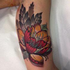 tattoo blume, lotusblume in rot und orange am oberarm, arm tätowieren