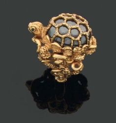CARTIER 1960s. Rare turtle-shaped ring formed a cabochon hematite in a golden cage mount. The body is formed of coiled serpents carved gold. Two emeralds for eyes. Signed and numbere