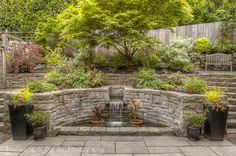 Great hardscaping idea for any yards that have a steep incline. Retaining wall gardens can be beautiful (though this one is more fountain/walk area than garden).