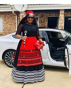 Beautiful Black Xhosa Umbhaco Dress With Red Apron, Red Beaded Cap and Beaded Stick South African Dresses, South African Traditional Dresses, African Wear Dresses, African Attire, African Print Dress Designs, African Print Fashion, Ankara Designs, African Design, African Prints