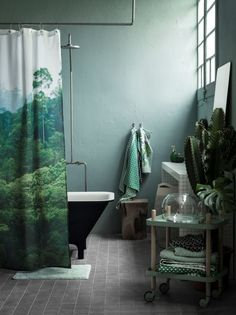 A minimalist bathroom with a touch of nature in relaxing green. By the tub is H&M's Rainforest shower curtain. They also had one with a conifer forest, but both seem to unavailable at the moment.