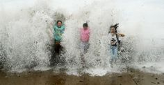 Crianças são atingidas por onda em praia da cidade de Qingdao, na China. A ressaca do mar foi provocada pela aproximação do tufão Chan Hom, que chegou a registrar ventos de mais de 120 km/h e fortes chuvas na região antes de se afastar da costa chinesa. Apesar de ter afetado cerca de 710 mil pessoas, o tufão não deixou nenhuma vítima no país.  Fotografia: Wang Haibin / Xinhua.
