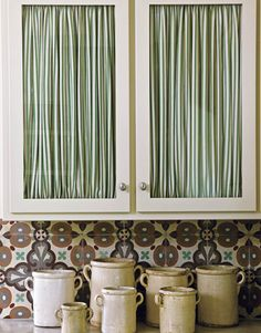 """Curtain Just One Cabinet  To shake things up, try adding a curtain to just one cabinet. """"Cabinet after cabinet, door after door gets boring,"""" says Shannon Bower, who added Carleton V's Wallace ticking in Green and Natural to this pair."""