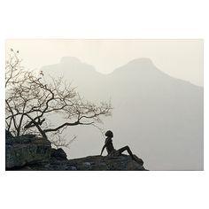 Veiled in haze, twin peaks tower above herdsman