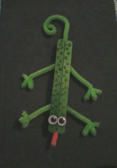 Popsicle stick & pipe cleaner lizard! Craft for kids age 4 to 6.   Glue two Popsicle sticks together (side by side) and let dry. Take two pipe cleaners and cut one in half. Bend pipe cleaner halves into legs with little toes on the ends. Bend whole pipe cleaner and curl for tail. Glue onto bottom of lizard body and let dry. Add two googly eyes and use glitter glue to make polka dots on lizard body.