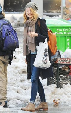 emma stone street style long black coat beige scarf, grey hat, tan backpack, dark blue skinny denim jeans and cute ankle boots beige and laced