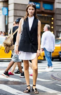 A high-concept tailored vest is worn over a white shirtdress, paired with flat sandals, a tote bag, and sunglasses