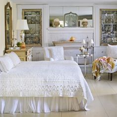 """Crisp white lace bedding, lighting fixtures with white shades, stained glass cabinet doors, and antique mirrors above a white fireplace"