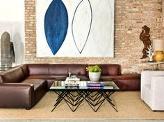 This modern and industrial living room from Wayfair Canada features a brown leather sectional, exposed brick walls, a large wall art piece, and a unique coffee table.