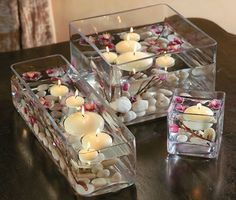 Floating candles, flowers and pebbles in glass containers for wedding table decor