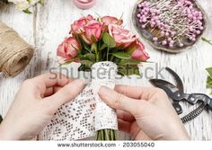 Florist at work. Woman making bouquet of pink roses - stock photo