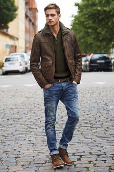 Brown leather aviator jacket, dark olive sweater, grey t shirt, brown belt, blue jeans, brown chukka boots