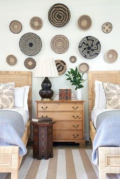Eclectic shared boys' bedroom boasts two twin rattan beds dressed in gray blankets accented with paisley pillows and placed on a tan striped rug on either side of a wood nightstand topped with a brown double gourd lamp located beneath wall mounted decorative wall baskets and lighting a Moroccan accent table placed between the beds.
